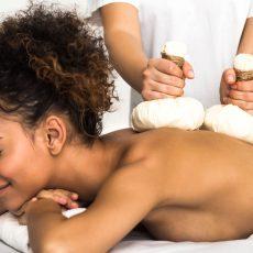 african-american-woman-enjoying-thai-herb-massage-YW3SP6N.jpg